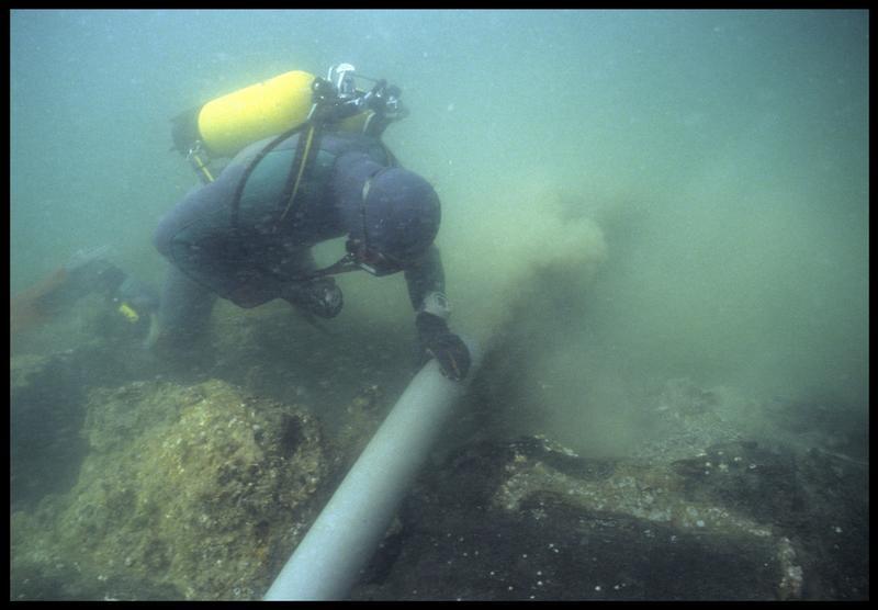 Vue sous-marine d'un plongeur à la déjection de la suceuse à eau(fouille M. L'Hour/Drassm, E. Veyrat/Drassm).