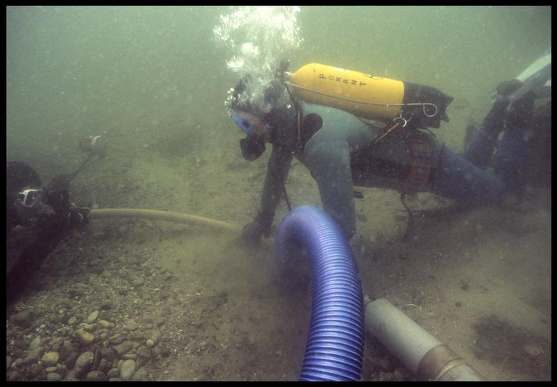 Vue sous-marine de deux plongeurs dévasant à la suceuse à eau(fouille M. L'Hour/Drassm, E. Veyrat/Drassm).
