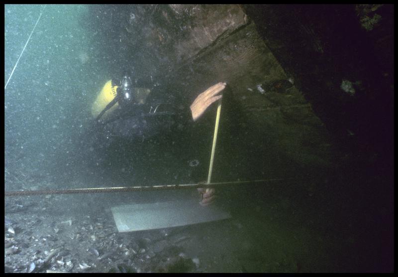 Vue sous-marine d'un plongeur effectuant des mesures sur la carène(fouille M. L'Hour/Drassm, E. Veyrat/Drassm).