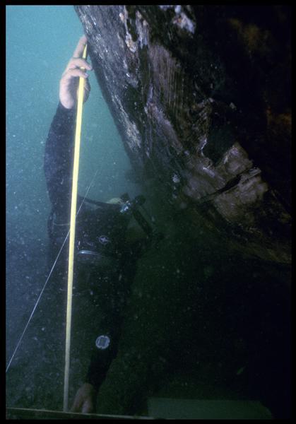 Vue sous-marine d'un plongeur effectuant les mesures sur la carène(fouille M. L'Hour/Drassm, E. Veyrat/Drassm).