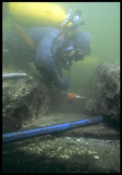 Vue sous-marine d'un plongeur effectuant un prélèvement de carène(fouille M. L'Hour/Drassm, E. Veyrat/Drassm).