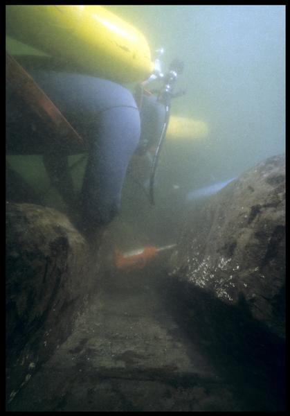 Vue sous-marine d'un plongeur effectuant le prélèvement sur la carène(fouille M. L'Hour/Drassm, E. Veyrat/Drassm).