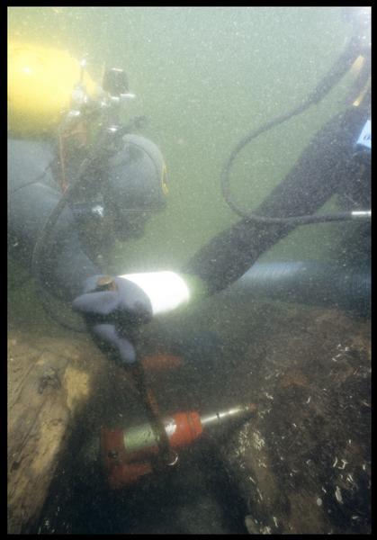 Vue sous-marine de deux plongeurs effectuant le prélèvement sur la carène(fouille M. L'Hour/Drassm, E. Veyrat/Drassm).