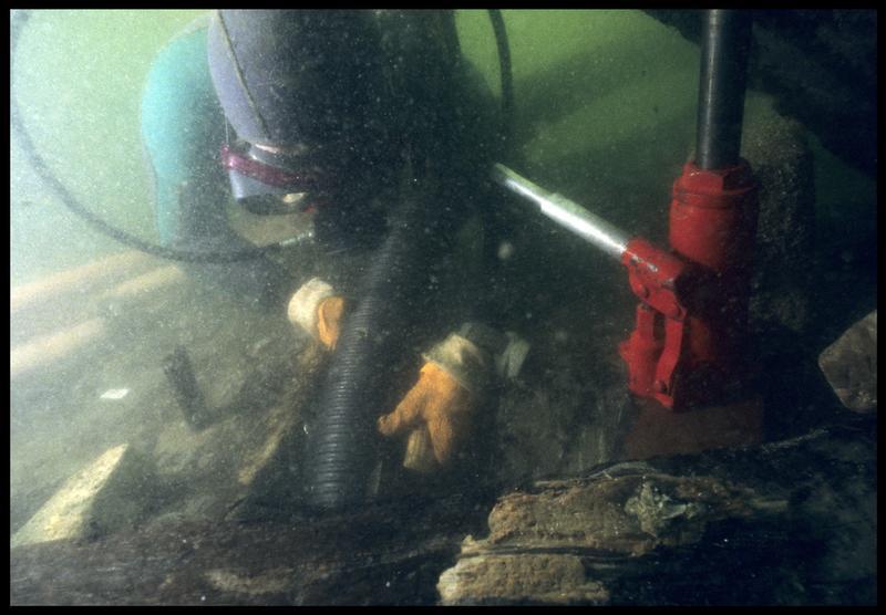 Vue sous-marine d'un plongeur dévasant à la suceuse à eau la carène(fouille M. L'Hour/Drassm, E. Veyrat/Drassm).