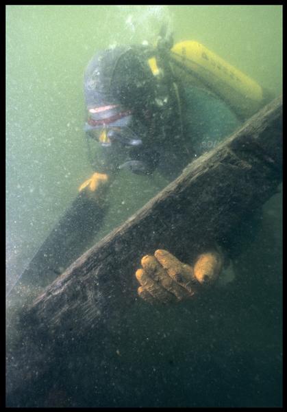 Vue sous-marine d'un plongeur sciant le prélèvement de la carène(fouille M. L'Hour/Drassm, E. Veyrat/Drassm).