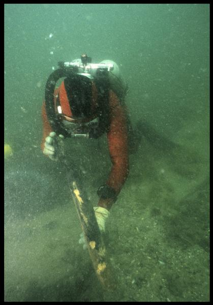Vue sous-marine d'un plongeur ramassant un fragment de bois(fouille M. L'Hour/Drassm, E. Veyrat/Drassm).