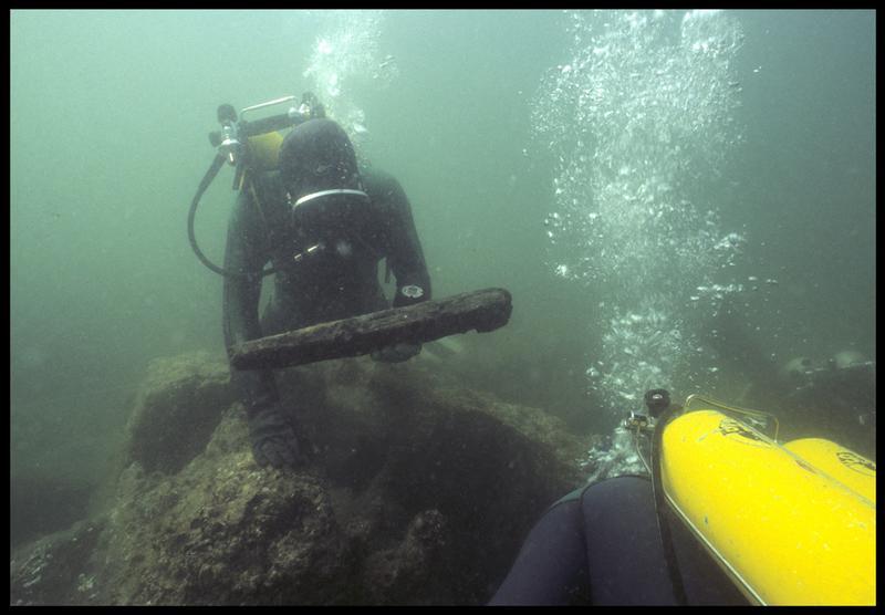 Vue sous-marine de deux plongeurs ramassant des fragments de bois(fouille M. L'Hour/Drassm, E. Veyrat/Drassm).
