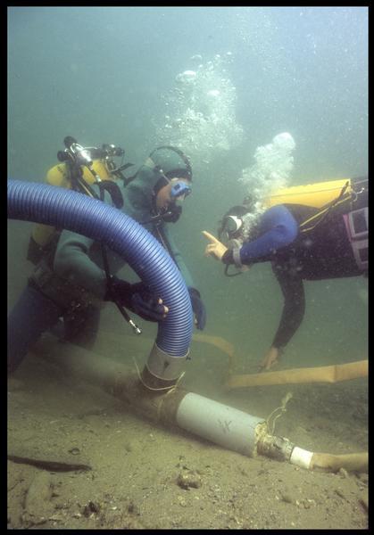 Vue sous-marine de deux plongeurs installant la suceuse à eau(fouille M. L'Hour/Drassm, E. Veyrat/Drassm).