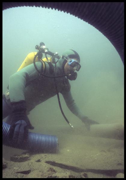 Vue sous-marine d'un plongeur installant la suceuse à eau(fouille M. L'Hour/Drassm, E. Veyrat/Drassm).