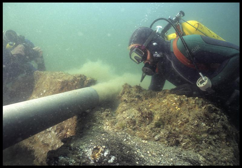 Vue sous-marine de deux plongeurs à la déjection de la suceuse à eau(fouille M. L'Hour/Drassm, E. Veyrat/Drassm).
