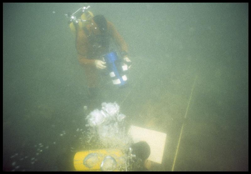Vue sous-marine d'un plongeur effectuant le relevé de la carène devant le vidéaste(fouille M. L'Hour/Drassm, E. Veyrat/Drassm).