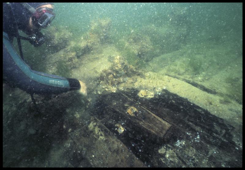 Vue sous-marine d'un plongeur dévasant l'écart long d'une varangue(fouille M. L'Hour/Drassm, E. Veyrat/Drassm).