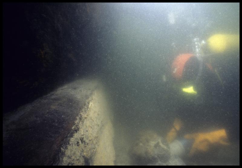 Vue sous-marine d'un plongeur dévasant à la suceuse à eau la carène (fouille M. L'Hour/Drassm, E. Veyrat/Drassm).
