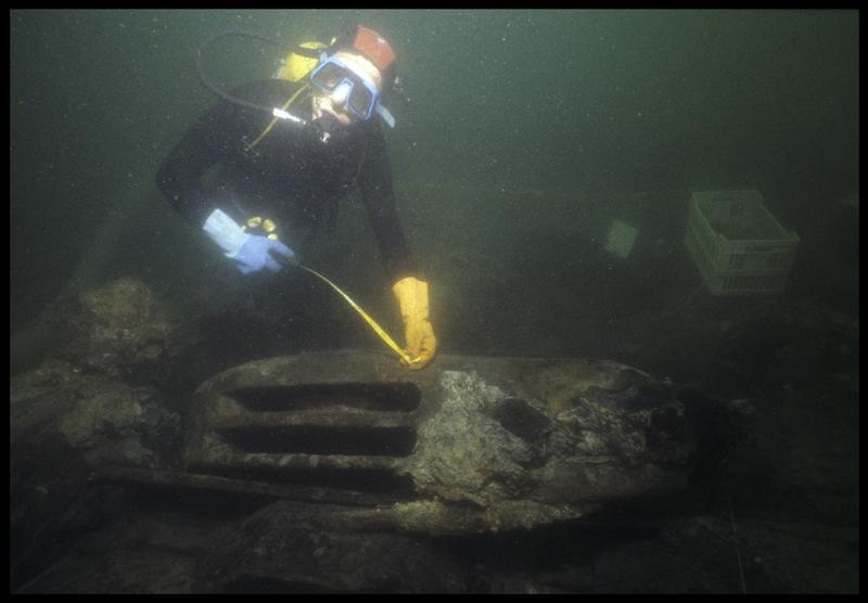 Vue sous-marine d'un plongeur mesurant une poulie de drisse de bois (fouille M. L'Hour/Drassm, E. Veyrat/Drassm).