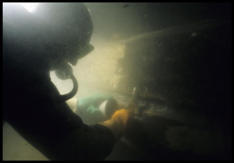 Vue sous-marine d'un plongeur prélevant du brai de la carène (fouille M. L'Hour/Drassm, E. Veyrat/Drassm).
