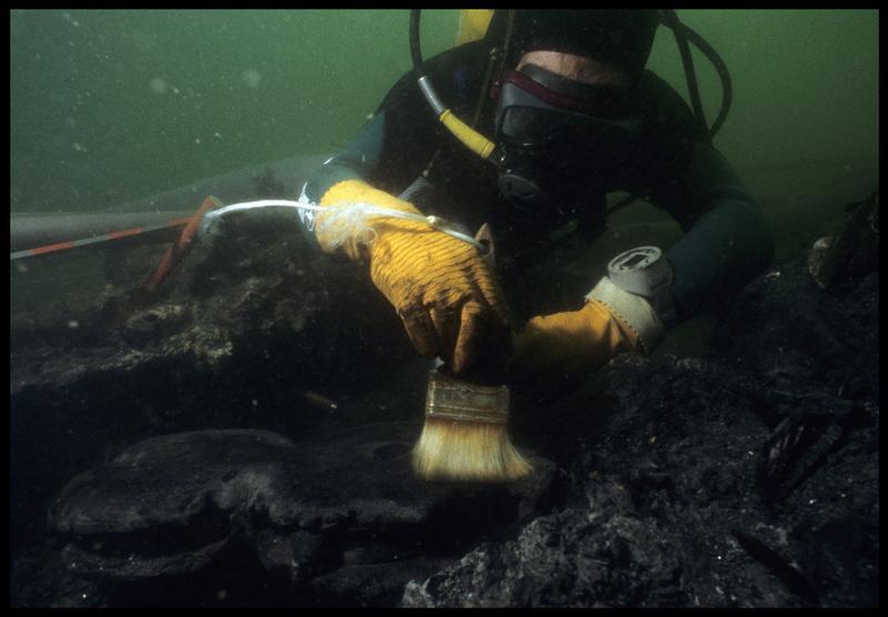 Vue sous-marine d'un plongeur nettoyant au pinceau une poulie violon en bois (fouille M. L'Hour/Drassm, E. Veyrat/Drassm).
