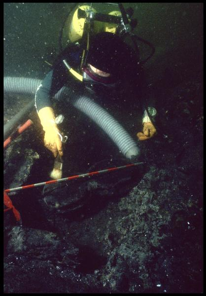 Vue sous-marine d'un plongeur dévasant à la suceuse à eau une poulie violon en bois (fouille M. L'Hour/Drassm, E. Veyrat/Drassm).