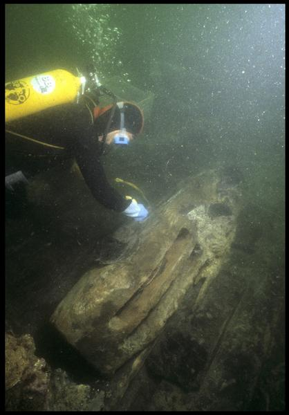 Vue sous-marine d'un plongeur mesurant d'une poulie de drisse en bois in situ (fouille M. L'Hour/Drassm, E. Veyrat/Drassm).