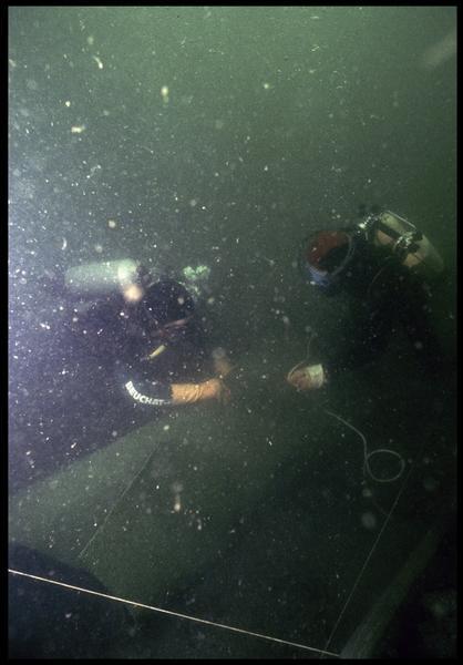 Vue sous-marine de deux plongeurs effectuant le levage d'une poulie de drisse en bois (fouille M. L'Hour/Drassm, E. Veyrat/Drassm).