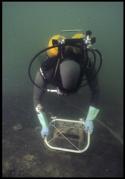 Vue sous-marine d'un plongeur effectuant le levage d'une poulie de bois (fouille M. L'Hour/Drassm, E. Veyrat/Drassm).