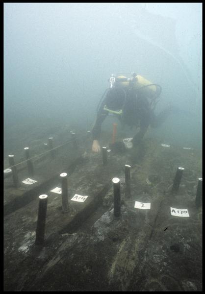Vue sous-marine d'un plongeur mesurant les gournables des membrures (fouille M. L'Hour/Drassm, E. Veyrat/Drassm).