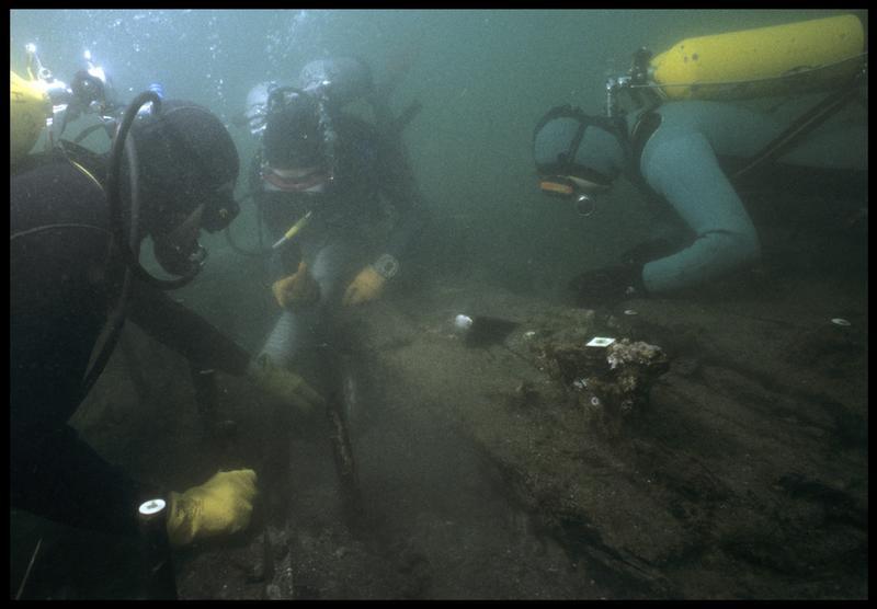 Vue sous-marine de trois plongeurs dévasant à la suceuse à eau la carène (fouille M. L'Hour/Drassm, E. Veyrat/Drassm).