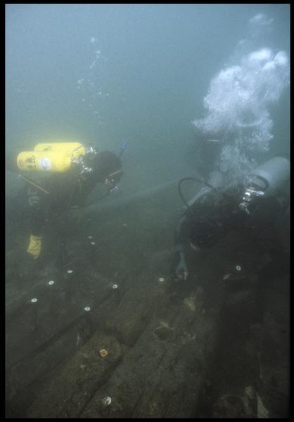 Vue sous-marine de deux plongeurs marquant les gournables de la carène (fouille M. L'Hour/Drassm, E. Veyrat/Drassm).