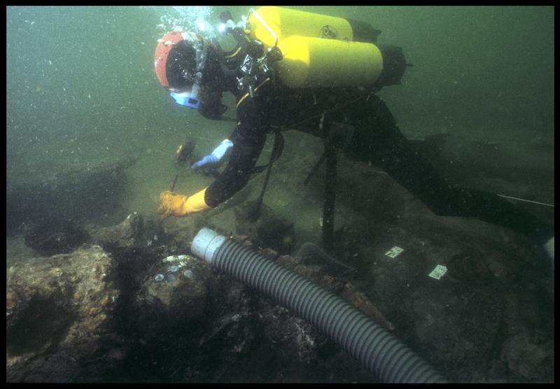 Vue sous-marine d'un plongeur cassant une concrétion métallique in situ (fouille M. L'Hour/Drassm, E. Veyrat/Drassm).