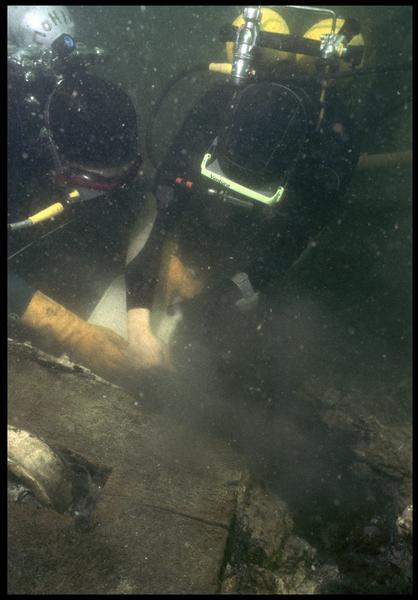 Vue sous-marine d'un plongeur dévasant à la suceuse à eau (fouille M. L'Hour/Drassm, E. Veyrat/Drassm).