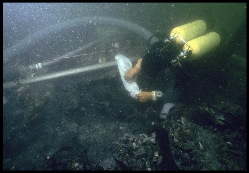 Vue sous-marine d'un plongeur mettant en sac du matériel pour le remonter (fouille M. L'Hour/Drassm, E. Veyrat/Drassm).