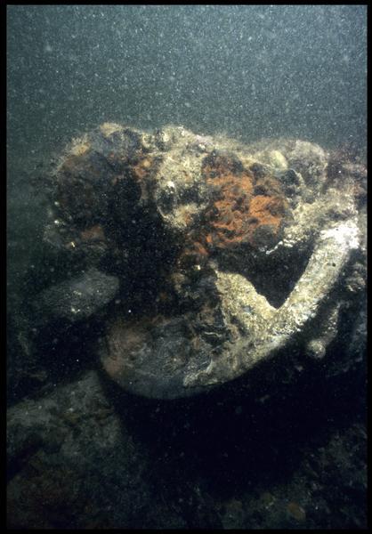 Vue sous-marine de détail d'une concrétion métallique avec une roue (fouille M. L'Hour/Drassm, E. Veyrat/Drassm).