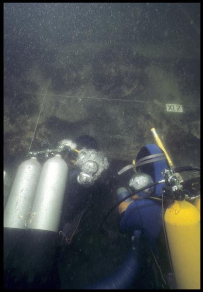 Vue sous-marine de deux plongeurs dévasant la carène à la suceuse à eau (fouille M. L'Hour/Drassm, E. Veyrat/Drassm).