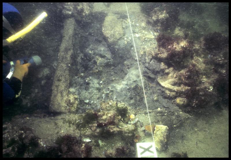 Vue sous-marine d'un plongeur dévasant la carène à la suceuse à eau (fouille M. L'Hour/Drassm, E. Veyrat/Drassm).