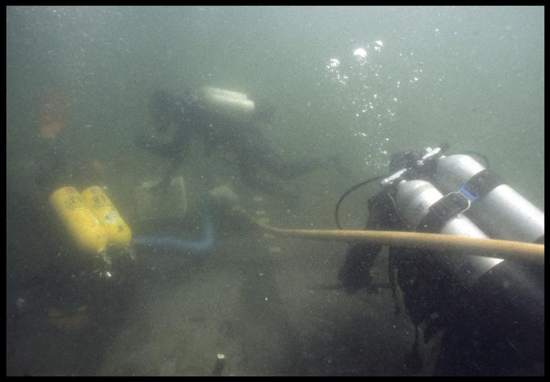 Vue sous-marine de trois plongeurs effectuant le prélèvement de la carène (fouille M. L'Hour/Drassm, E. Veyrat/Drassm).