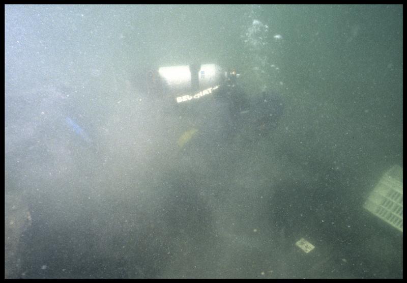 Vue sous-marine d'un plongeur effectuant un prélèvement de la carène (fouille M. L'Hour/Drassm, E. Veyrat/Drassm).