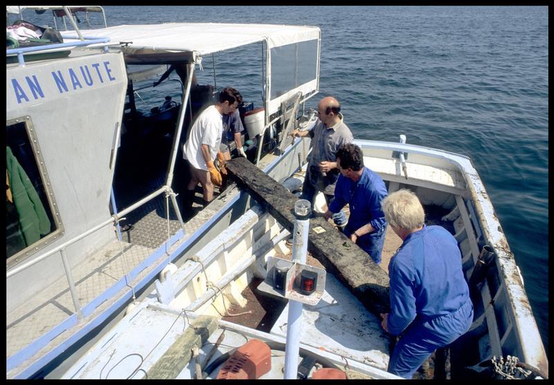 Vue du transport d'un prélèvement de la carène sur une embarcation de pêcheur (fouille M. L'Hour/Drassm, E. Veyrat/Drassm).