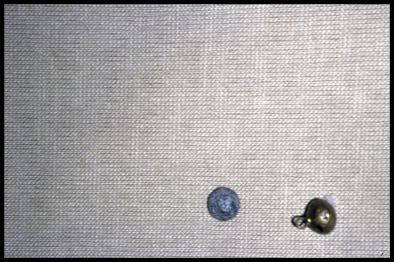 Vue d'un bouton de métal et d'un grelot (fouille M. L'Hour/Drassm, E. Veyrat/Drassm).