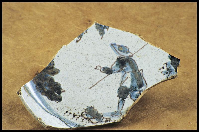 Vue d'un fragment de faïence avec un décor bleu de personnage (fouille M. L'Hour/Drassm, E. Veyrat/Drassm).