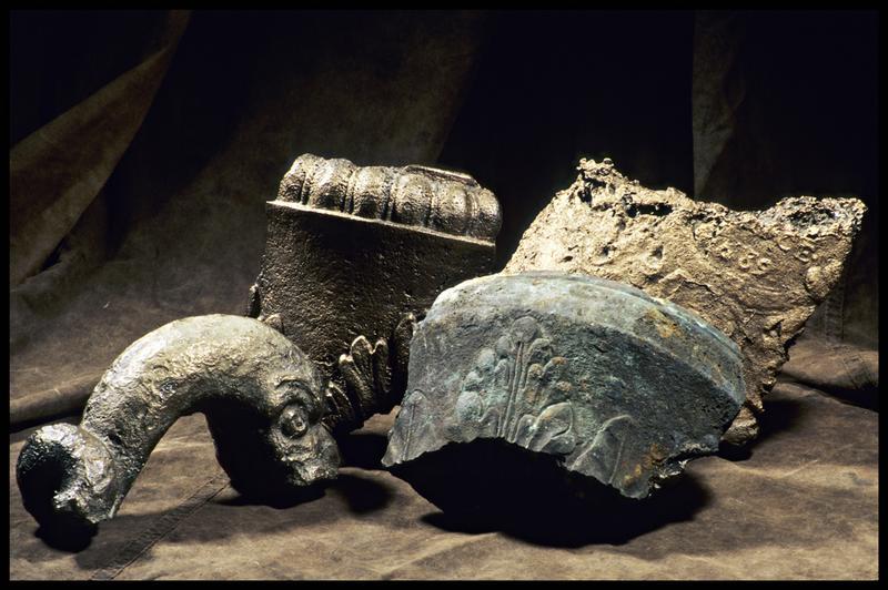 Vue de plusieurs éléments de métal avec des décors fleurdelisés (fouille M. L'Hour/Drassm, E. Veyrat/Drassm).