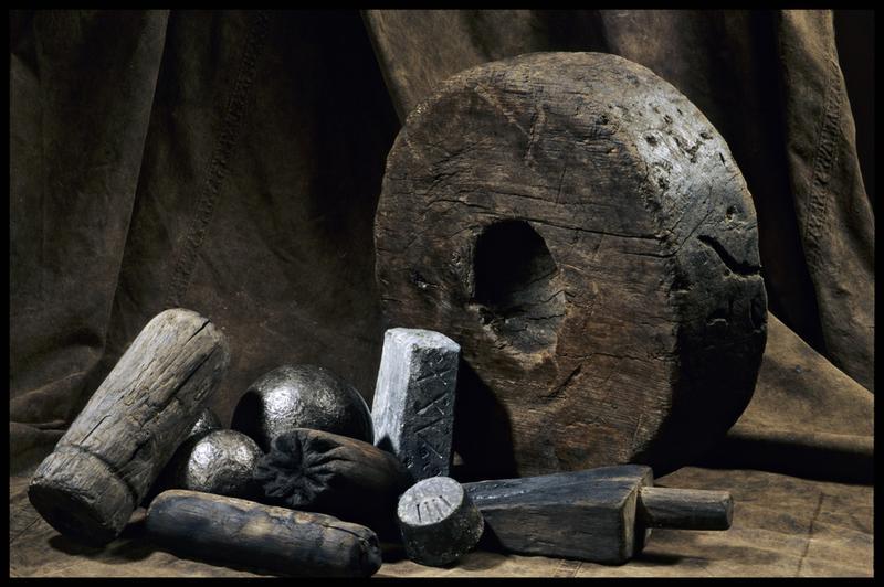 Vue d'une roue d'affût de bois, de deux lingots de plomb, d'éléments d'accastillage en bois (coin, et manche) et de boulets de canon (fouille M. L'Hour/Drassm, E. Veyrat/Drassm).