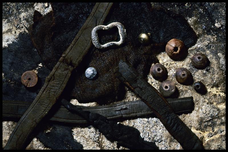 Vue d'éléments de cuir (ceintures), tissus, de métal (boucle de ceinture, grelot et bouton) et de bois (boutons) (fouille M. L'Hour/Drassm, E. Veyrat/Drassm).