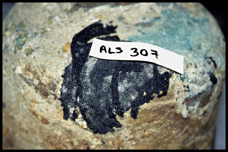 Vue de détail d'un fragment de tissu sur la cloche (fouille G. Watts).