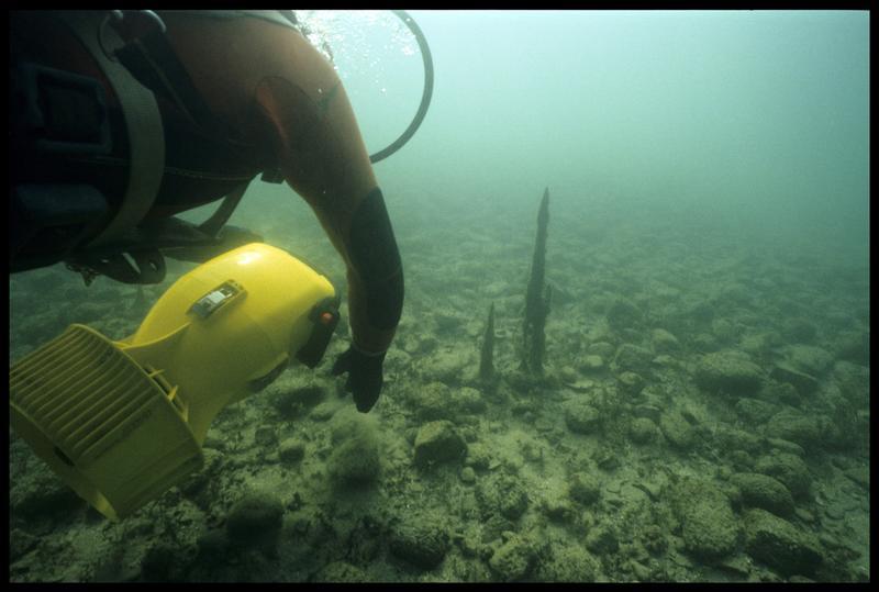 Vue sous-marine d'un plongeur et de son locoplongeur au dessus de pieux de bois (fouille A. Marguet/Drassm).
