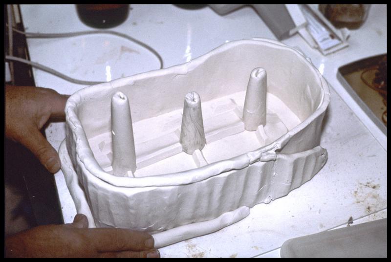 Vue de la mise en place du muret de plastiline autour de l'objet enchassé dans la plastiline (CNRAS).