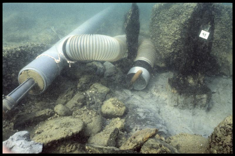 Vue sous-marine de deux pieux de bois (dont le 19) et de la suceuse à eau (fouille A. Marguet/Drassm).