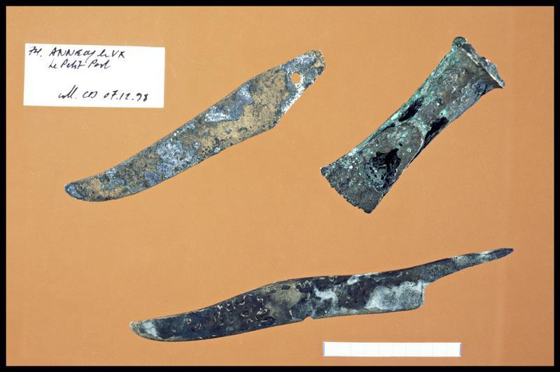 Vue de deux lames de couteau et d'un élément de bronze (fouille C. Dupont).