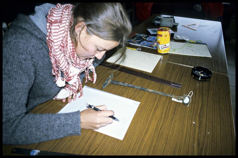 Vue du travail d'une dessinatrice sur une pièce de métal (fouille E. Rieth).