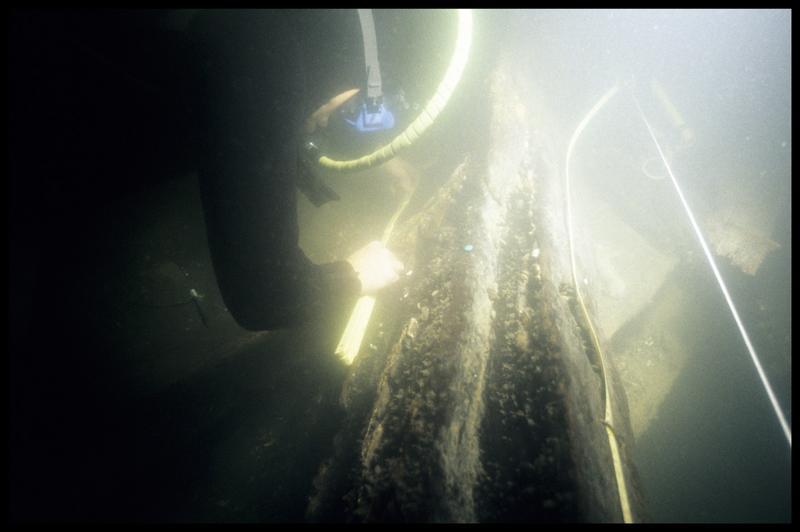 Vue sous-marine d'un plongeur effectuant un relevé sur la carène (fouille E. Rieth).