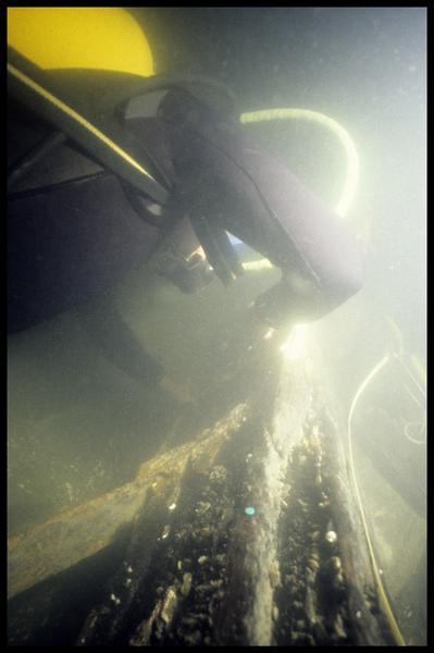 Vue sous-marine d'un plongeur effectuant des relevés sur la carène (fouille E. Rieth).