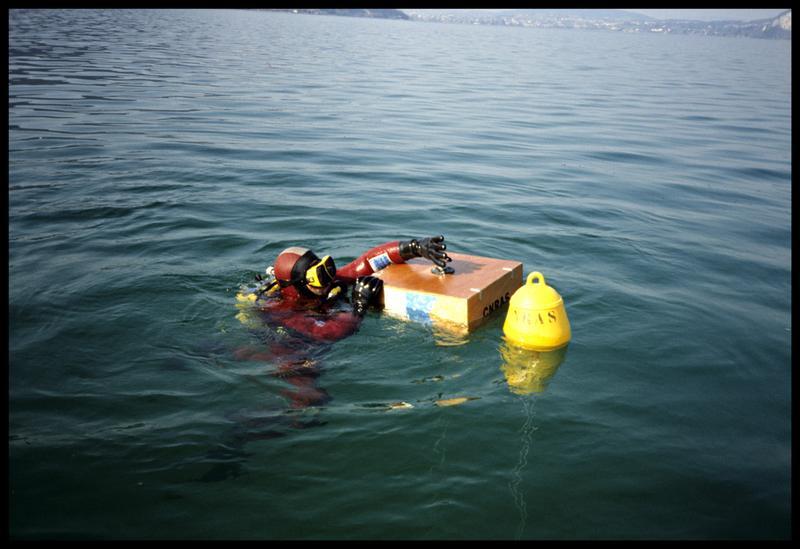 Vue d'un plongeur mettant en place la caisse topographique sur une balise (fouille CNRAS).